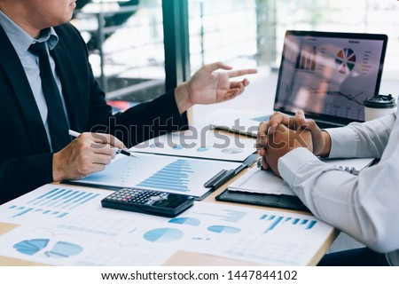 Male manager is explaining about the company's cost graph on the laptop computer for employees to listen to and share the analysis together. #1447844102