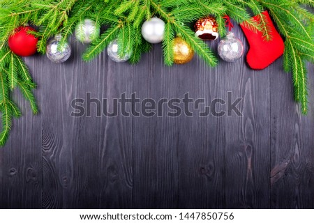 Christmas festive border, New Year decorative frame, silver balls decorations, red gift sock on green pine branches on black wooden background closeup, winter holidays design, free copy space for text #1447850756