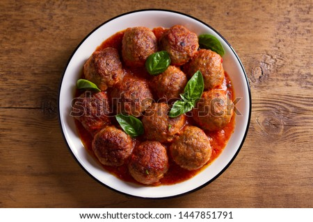 Meatballs in tomato sauce, garnished with basil in bowl on wooden table. View from above, top studio shot #1447851791