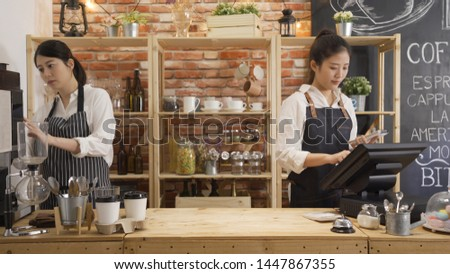 two elegant coffeehouse staff working behind counter in cafe shop. young girl waitress checking customer order with note and tablet. woman barista using machine make beverage in modern coffee store. #1447867355