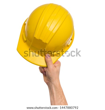 Male Hand with yellow safety helmet. Human Hand holding hard hat, Isolated on White Background. #1447880792