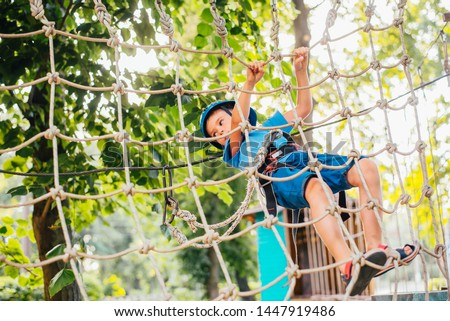 Little cute boy enjoying activity in a climbing adventure park on a summer sunny day. toddler climbing in a rope playground structure. Safe Climbing extreme sport with helmet and Carabiner. insurance #1447919486