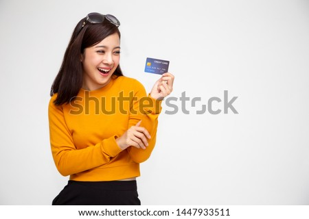 Happy Asian woman in yellow shirt holding credit card or cash advances, Pay instead of money and specially curated benefits for lady card concept #1447933511