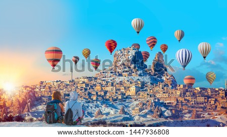 Hot air balloon flying over spectacular Cappadocia - Girls watching hot air balloon at the hill of Cappadocia #1447936808