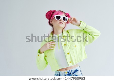 woman with pink hair with glasses on a light background