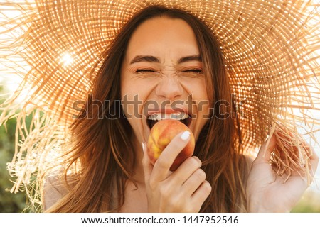 Photo of young positive happy cheery woman in hat posing outdoors at the nature green grass near beach eat peach. #1447952546