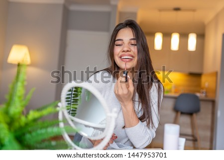 Portrait of a beautiful woman, dyes her lips lipstick, looking in the mirror. Beautiful girl is using a lipgloss while looking into the mirror at home. Woman lipstick mirror #1447953701