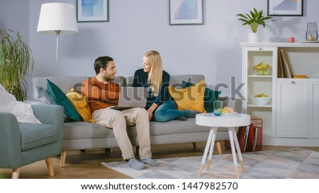 Happy Lovely Couple Sits on a Sofa at Home, Boyfriend Holds Laptop on Knees, Browsing through Internet, Doing e-Shopping, Using Streaming Services. Happy Family in Cozy Living Room. #1447982570