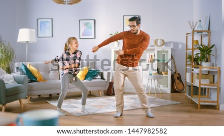 Happy Little Girl Dances with Young Father in the Middle of the Living Room. Happy Family Time, Father and Daughter Dancing at Home. #1447982582