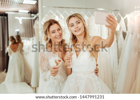 Memorizing the moment. Two gorgeous brides taking a selfie and drinking champagne in a wedding salon.