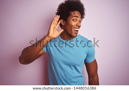 African american man with afro hair wearing blue t-shirt standing over isolated pink background smiling with hand over ear listening an hearing to rumor or gossip. Deafness concept. #1448016386
