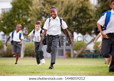 Excited Elementary School Pupils Wearing Uniform Running Across Field At Break Time Royalty-Free Stock Photo #1448019212