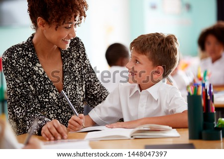 Woman Elementary School Teacher Giving Male Pupil Wearing Uniform One To One Support In Classroom Royalty-Free Stock Photo #1448047397