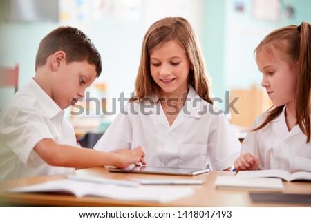 Three Elementary School Pupils Wearing Uniform Using Digital Tablet At Desk #1448047493