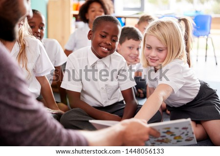 Male Teacher Reading Story To Group Of Elementary Pupils Wearing Uniform In School Classroom Royalty-Free Stock Photo #1448056133