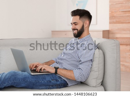 Handsome young man working with laptop on sofa at home #1448106623