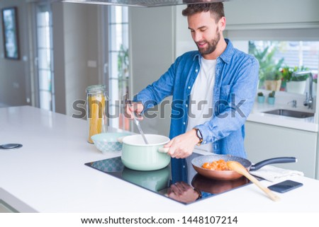 Handsome man cooking pasta at home #1448107214