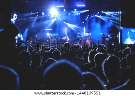 A crowd gathers infront of a concert lit in blue #1448109551