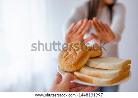 Gluten intolerance concept. Young girl refuses to eat white bread. Celiac Disease. No bread, thanks: gluten-free concept. Woman on gluten free diet #1448191997