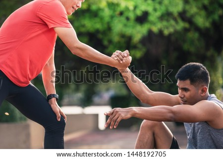 Helping hand outstretched for salvation . Strong hold. Running man helping his friend. Man help each other to run on the running track. #1448192705