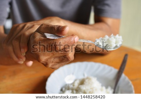 Elderly man is holding his hand while eating because Parkinson's disease.Tremor is most symptom and make a trouble for doing activities such as eat or drink.Health care or elderly concept. #1448258420