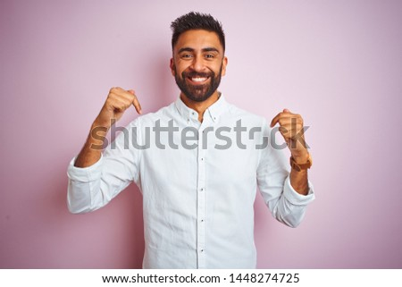 Young indian businessman wearing elegant shirt standing over isolated pink background looking confident with smile on face, pointing oneself with fingers proud and happy. #1448274725
