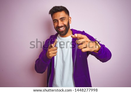 Young indian man wearing purple sweatshirt standing over isolated pink background pointing fingers to camera with happy and funny face. Good energy and vibes. #1448277998