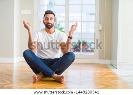 Handsome hispanic man wearing casual t-shirt sitting on the floor at home relax and smiling with eyes closed doing meditation gesture with fingers. Yoga concept. #1448280341