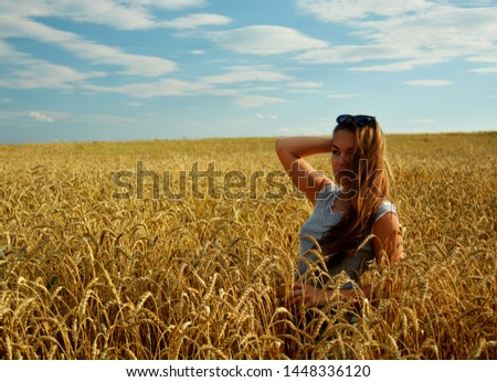 Young beautiful girl stands on a field in wheat under sunlight. #1448336120