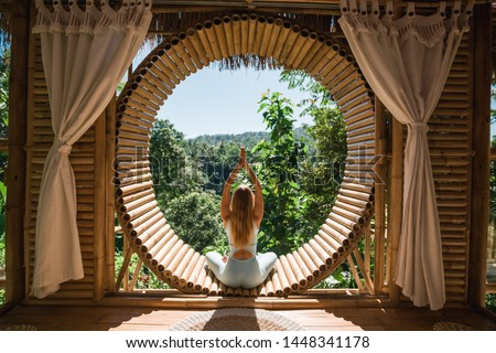 Young girl doing yoga outdoor. Young woman practicing yoga in bamboo house, nature on background.Female happiness.Caucasian woman practicing yoga on vacation on Bali island #1448341178