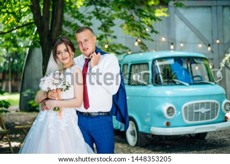 Beautiful young guy and girl in their wedding day in the park drinking tea at a table. Blue car in the background #1448353205