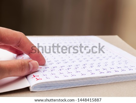 Learn Arabic writing. Notebook filled with Arabic letters. Education concept