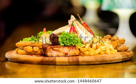 Restaurant food. Wooden board with lot french fries fish sticks burrito and meat steak served with salad. Pub menu snack. High calorie snack for group friends. Tasty delicious snacks. Snack for beer. #1448460647
