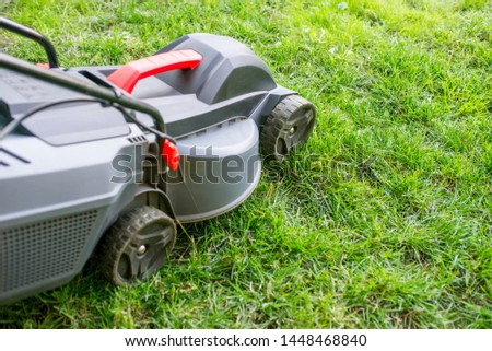 Mowing a lawn with a lawn mower. Lawn mowers cut grass. Garden work concept background. #1448468840
