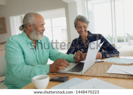 Side view of African-American couple doing finances on the table indoor. Authentic Senior Retired Life Concept #1448470223
