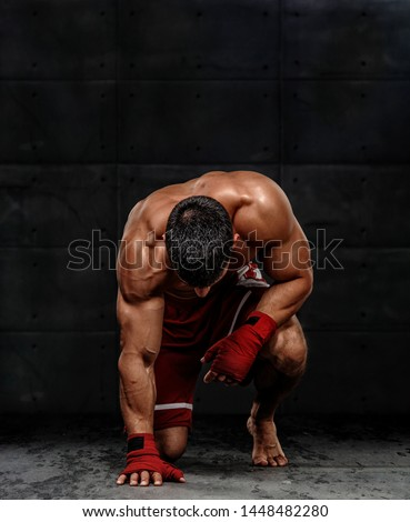 MMA Fighter Kneeling on the Floor Before the Fight Royalty-Free Stock Photo #1448482280