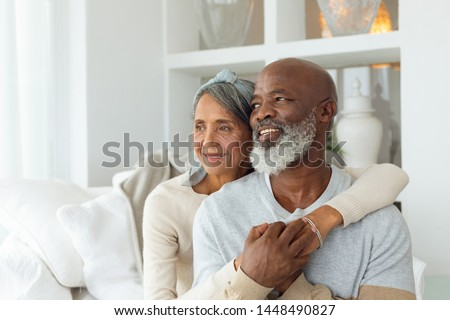 Front view of senior diverse couple sitting on a white couch in beach house. Authentic Senior Retired Life Concept #1448490827