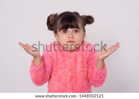 I don't know. Little kid isolated on grey background being at a loss, showing helpless gesture with arm and hands. Mouth curved as if he does not know what to do #1448502521
