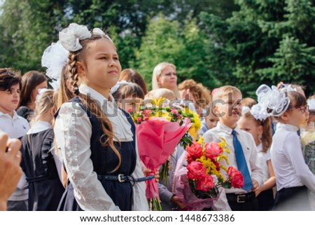NOVOKUZNETSK, KEMEROVO REGION, RUSSIA - SEP, 1, 2018: Meeting with the first-grade pupils and teacher at schoolyard. The day of knowledge in Russia. #1448673386