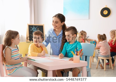 Little children with kindergarten teacher drawing at table indoors. Learning and playing #1448769377