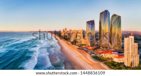 Rising sun shining on modern urban towers of Surfers paradise in Australian Gold Coast facing endless waves of Pacific ocean - aerial panoramic view. #1448836109