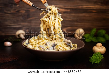Homemade Italian fettuccine pasta with mushrooms and cream sauce (Fettuccine al Funghi Porcini). Traditional Italian cuisine. Served on a dark table with a rustic wooden background. Close-up #1448882672