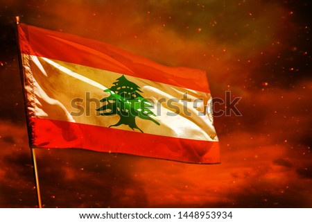 Fluttering Lebanon flag on crimson red sky with smoke pillars background. Lebanon problems concept. Royalty-Free Stock Photo #1448953934