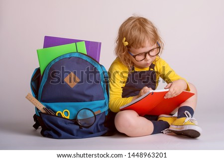 Children go back to school. Little happy  girl doing homework at home with backpack full of books, pencils. Pupil reading a book, writing and painting.  Kid is drawing. Child in glasses.  #1448963201