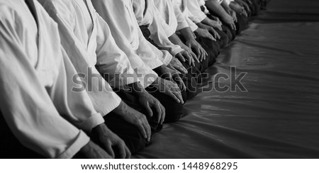 Black and white image of aikido. Men are sporsmen. Aikido workshop. A number of black belt practitioners in traditional uniform, white kimano and black hakama. Royalty-Free Stock Photo #1448968295