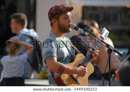 Copenhagen/Denmark - 21 June 2019: A Busker singing and playing guitar on the streets of Copenhagen.  #1449100253