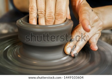 Workshop molding of clay on a potter's wheel. Craftsman molding the clay into the desired shape on potter's wheel. Close-up picture. Pottery, workshop, ceramics art concept.