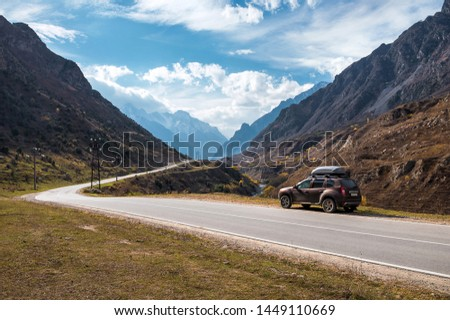 Crossover car on the asphalt road in the mountains at sunny weather #1449110669