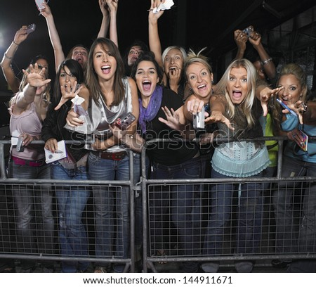 Fans leaning over barrier and screaming