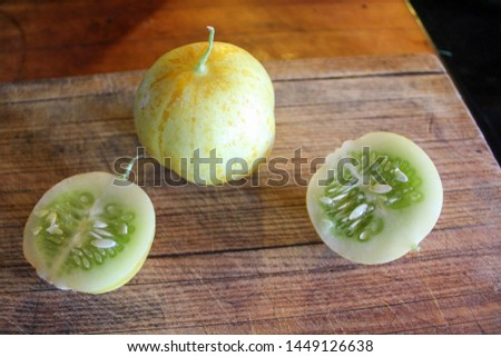 High view of Lemon Cucumbers on rustic wooden cutting board #1449126638